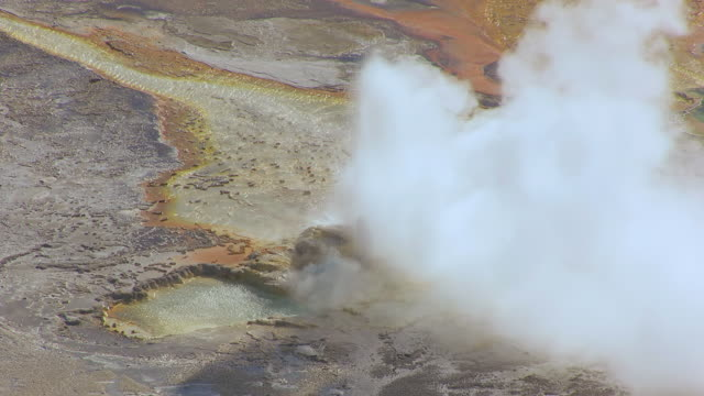 ms aerial ts shot of steam rising from clepsydra geyser in yellowstone national park / wyoming, united states - イエローストーン国立公園点の映像素材/bロール