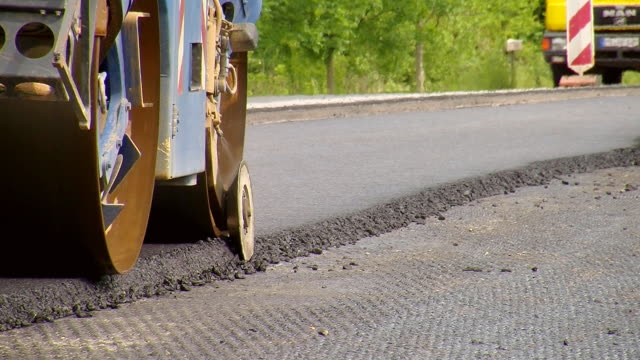 ms shot of steam roller cutting edges of excess of material on resurfacing of road / saarburg, rhineland-palatinate, germany - road construction stock videos and b-roll footage