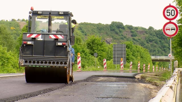 ws shot of steam roller cutting edges of excess of material on resurfacing of road / saarburg, rhineland-palatinate, germany - roadworks stock videos & royalty-free footage