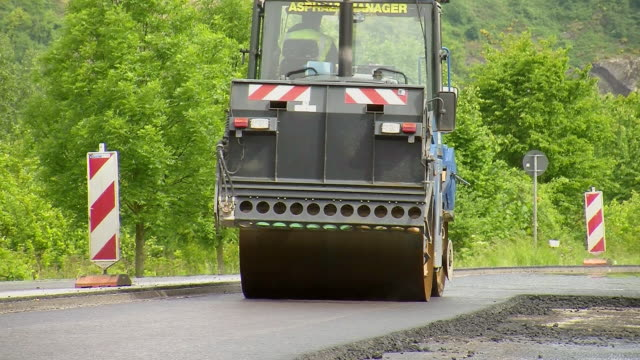 ms shot of steam roller working on road re surfacing of road / saarburg, rhineland-palatinate, germany - surfacing stock videos & royalty-free footage
