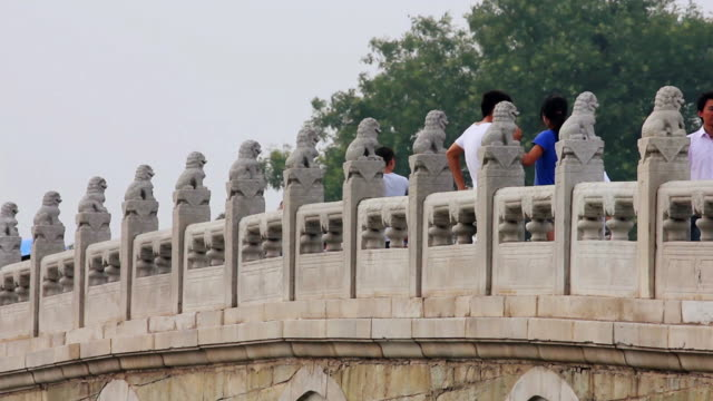 ms shot of stone lions on 17 arch bridge in summer palace / beijing, china - stone object stock videos & royalty-free footage