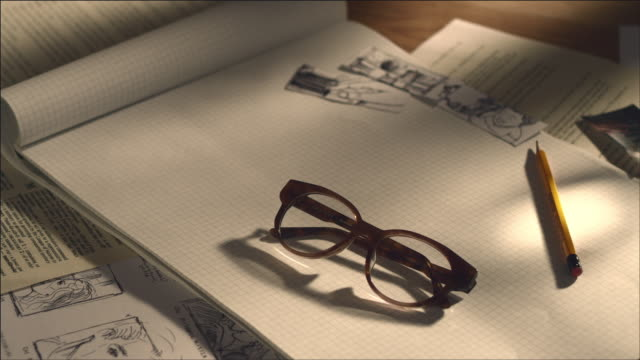 shot of storyboard, note pad with glasses - occhiali da vista video stock e b–roll