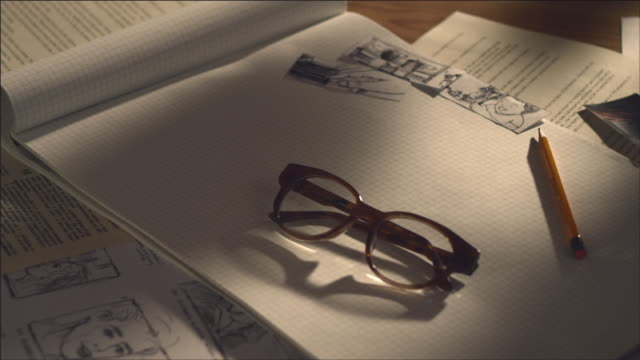 vidéos et rushes de shot of storyboard, note pad with glasses - rough