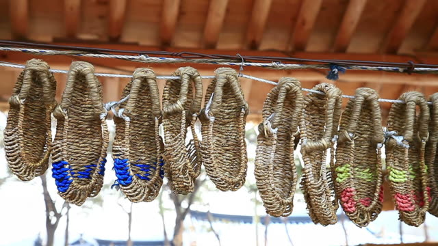 CU Shot of straw shoes hanging on string / Jeju, Jeju-do, South Korea