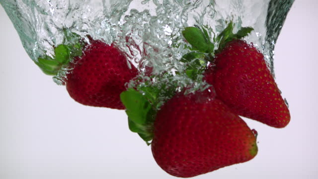 CU SLO MO Shot of Strawberries sinking in water / Toronto, Ontario, Canada