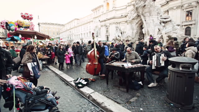 WS Shot of street artists entertaining tourists in Piazza Novena with Gipsy band playing live music / Rome, Italy