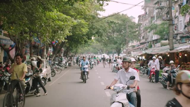 MS SLO MO POV Shot of street buzzing with life and motorbikes, next to market / Hanoi, Vietnam
