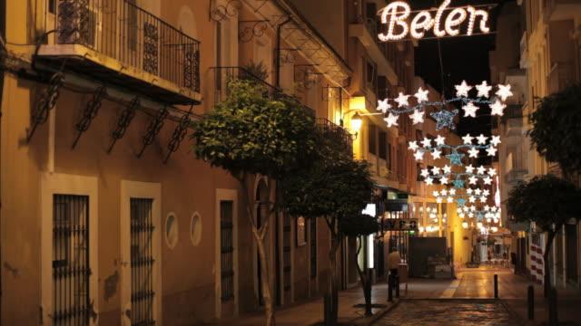 ms shot of street decorated with christmas lights and pedestrian walking / algeciras, cadiz, spain  - cádiz stock videos and b-roll footage