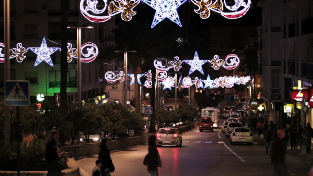 ms shot of street decorated with christmas lights and traffic circulating / algeciras, cadiz, spain  - cádiz stock videos and b-roll footage