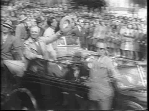 Shot of street in San Francisco with crowds at the side of the street and a parade of cars beginning to go down street / montage of President Harry S...