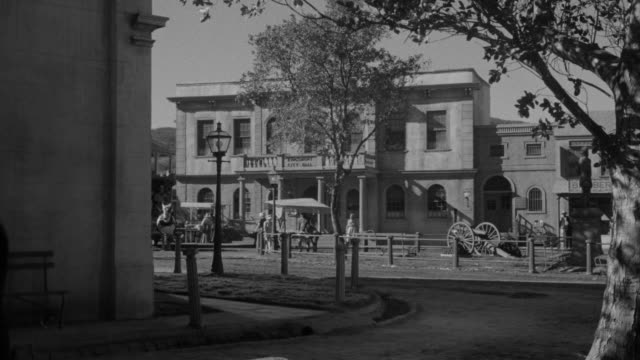 MS Shot of Street scene with horse and carriage riders, people walking at western town