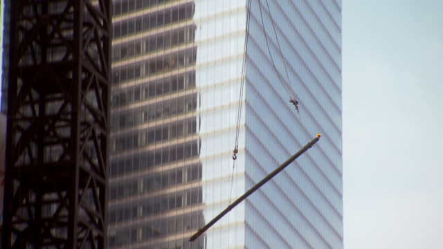 ms ts shot of street scene with one world trade center building under construction and crane lifting up steel bar into air / new york, united states - tilt up stock videos & royalty-free footage