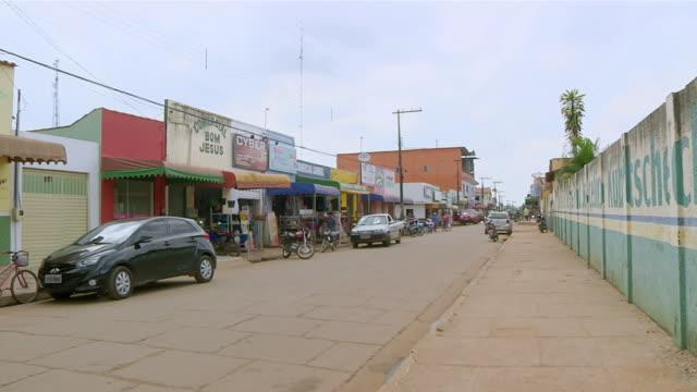 WS Shot of street shops and parked vehicle along road side in village / Serra Pelada, Para, Brazil