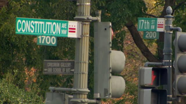 ms shot of street sign for 1700 block of constitution avenue and 17th street / washington, district of columbia, united states - targa con nome della via video stock e b–roll