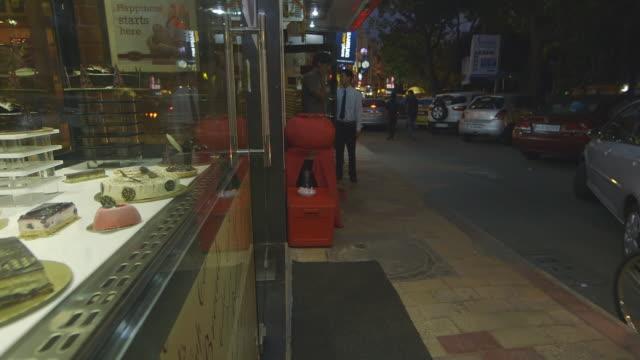 MS PAN Shot of street to cake shop window display / New Delhi, India