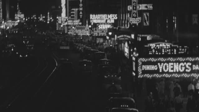 ms shot of street traffic and crowded sidewalks at broadway strand theatre in manhattan at night - broadway manhattan video stock e b–roll