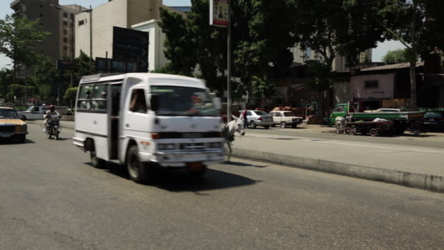 ms pan shot of street traffic and donkey cart / cairo, egypt - esel stock-videos und b-roll-filmmaterial