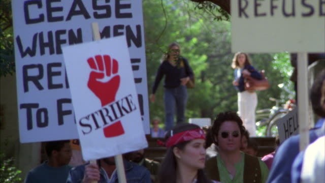 ms shot of students walking with anti war slogans signs at college or university campus for anti war demonstrators - placard stock videos & royalty-free footage