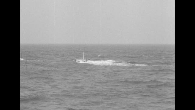 vídeos de stock, filmes e b-roll de aerial shot of submarine sailing on water's surface / vs submarine submerges / ms sailor turns and looks thru periscope / ms submarine emerges from... - documentário
