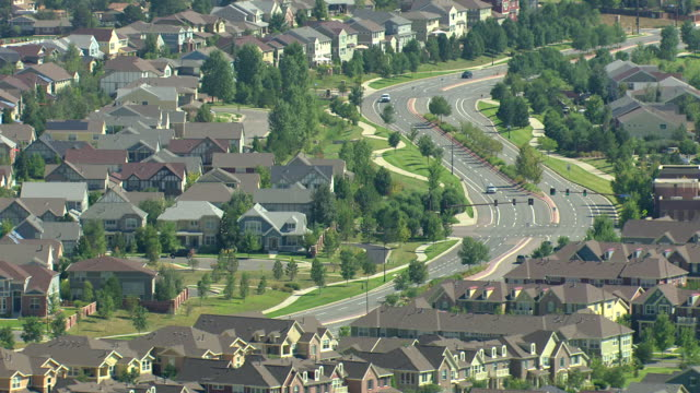 ms ds aerial shot of suburban houses with cars driving on streets and trees lining streets / denver, colorado, united states - housing development stock videos & royalty-free footage