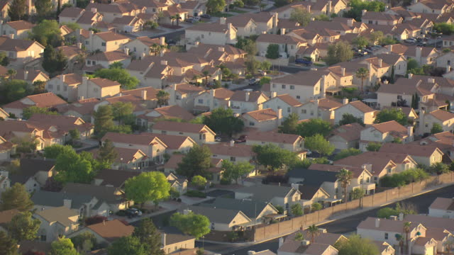 MS AERIAL Shot of suburban neighborhood with identical houses and streets with cars in morning / Las Vegas, Nevada, United States