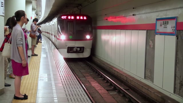 ms shot of subway arriving then passengers get on and off subway train / tokyo, japan - railway station platform stock videos & royalty-free footage