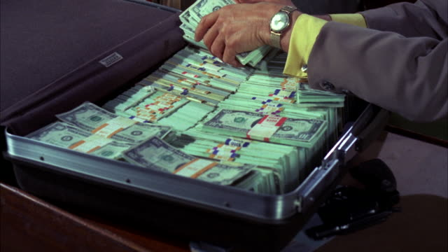 vídeos de stock, filmes e b-roll de ms shot of suitcase with bundles of money - stack