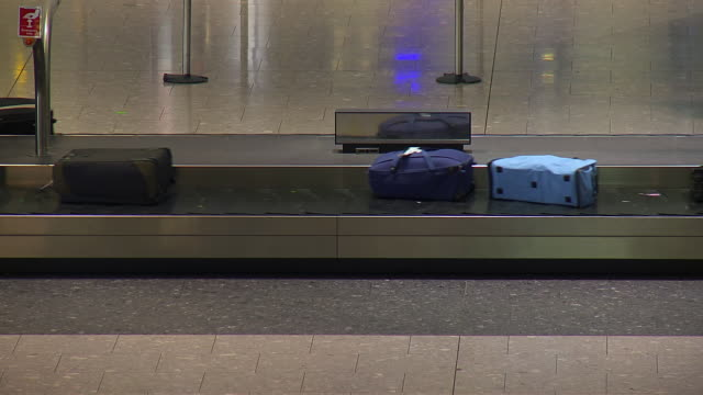 MS T/L Shot of Suitcases moving along baggage reclaim belt in Heathrow airport / London, United Kingdom