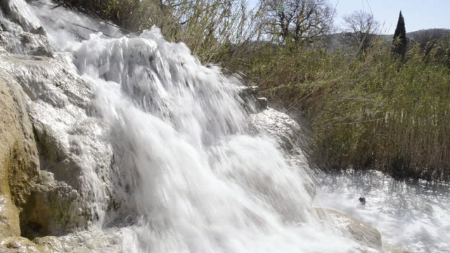 stockvideo's en b-roll-footage met ms shot of sulphurous water plunges in waterfall in thermal pools / saturnia, tuscany, italy - thermaalwater