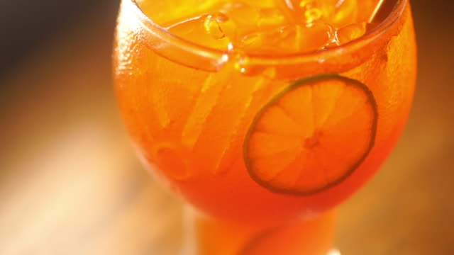 3 shot of summer refreshing with an iced orange cocktail with slices of lime in a glass against dark background. - sour taste stock videos & royalty-free footage