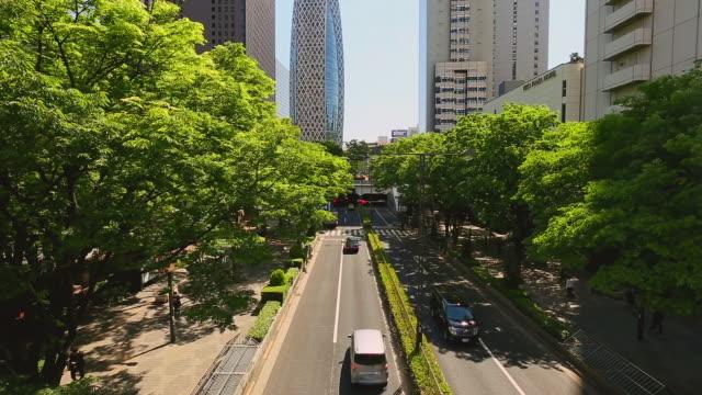 MS TU Shot of sun and commuters and cars and skyscraper under lined fresh green trees street at district of West Shinjuku / Shinjuku ku, Tokyo, Japan