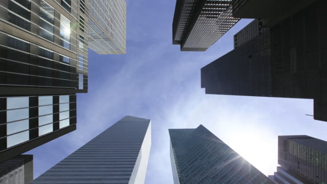 ws t/l pan la shot of sun and moving clouds above skyscraper at midtown / new york, united states - directly below stock videos & royalty-free footage