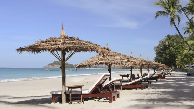 WS Shot of Sun beds and straw parasol in row on beach / Ngapali, Rakhine State, Myanmar