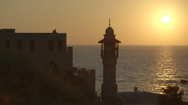 ms shot of sun begins to set on mediterranean sea with al bahr mosque tower / jaffa, tel, aviv israel - jaffa stock-videos und b-roll-filmmaterial