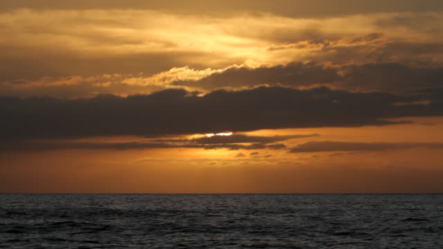 vídeos y material grabado en eventos de stock de ws shot of sun coming out of clouds at sunset over pacific ocean / polihe beach, kauai hawaii, united states - un minuto o más