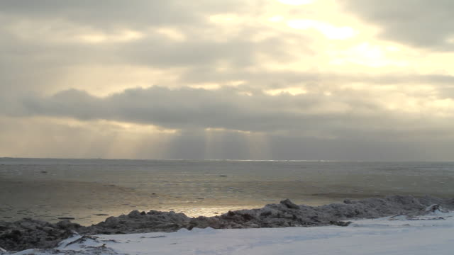 stockvideo's en b-roll-footage met ws shot of sun peers through clouds over ocean in distance / arviat, nunavut, canada - wiese
