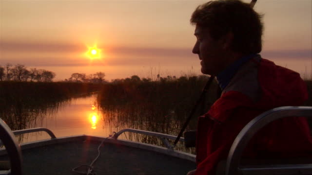 vidéos et rushes de ms pov shot of sun sets with man on boat / ghanzi district, ghanzi district, botswana - wiese