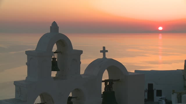 ms shot of sun setting and church bell at village oia / santorini, cyclades, greece - oia santorini stock videos & royalty-free footage