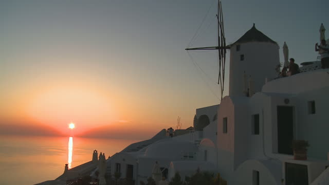 MS Shot of Sun setting at village Oia with Ocean / Santorini, Cyclades, Greece