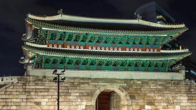 cu t/l zo shot of sungnyemun gate and traffic moving / seoul, south korea - 乗り物の明かり点の映像素材/bロール