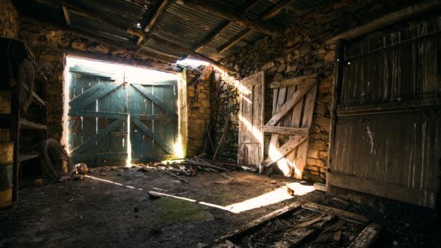 vídeos de stock, filmes e b-roll de ws t/l shot of sunlight streams through cracks around old barn door / caledon, western cape, south africa - celeiro