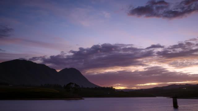 stockvideo's en b-roll-footage met ws t/l shot of sunrise over hill shows beautiful lake in prosperous valley / heidelberg, western cape, south africa - stilstaande camera