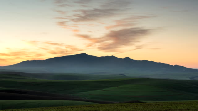 ws t/l shot of sunrise showing wheat filled hills lighting up with sunlight as sun rises in sky / caledon, western cape, south africa - hill stock-videos und b-roll-filmmaterial