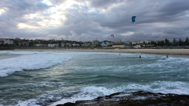 4k shot of surf and kite boarders on bondi beach - kite sailing stock videos & royalty-free footage