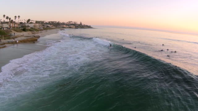 WS AERIAL SLO MO Shot of surfers and people enjoying at beach la jolla at sunset / San Diego, California, United States