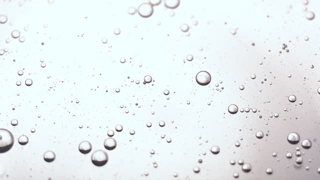 CU SLO MO Shot of suspended spheres of air in oil rest on surface of water and moving about slowly / United Kingdom