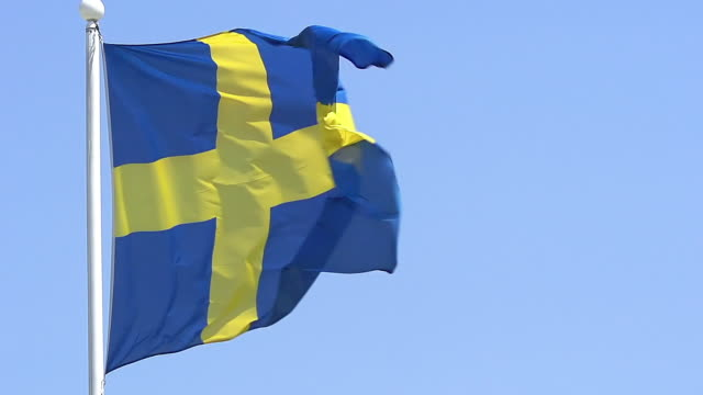 ms slo mo shot of sweden flag waving in wind / caen, normandy, france - swedish flag stock videos and b-roll footage