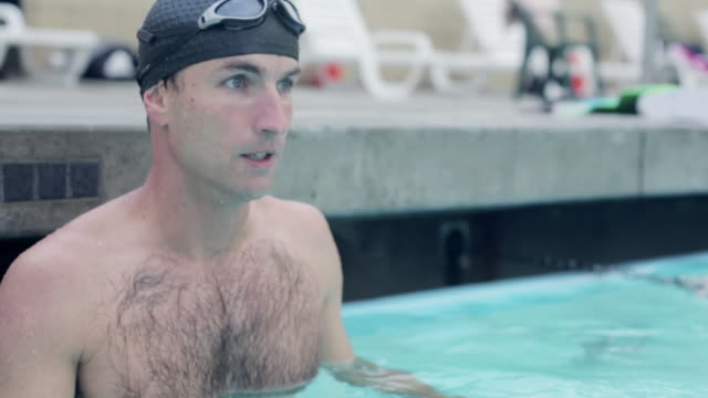 ms shot of swimmer puts on goggles and pushes off from side of pool / los angeles, california, united states  - one mid adult man only stock videos & royalty-free footage
