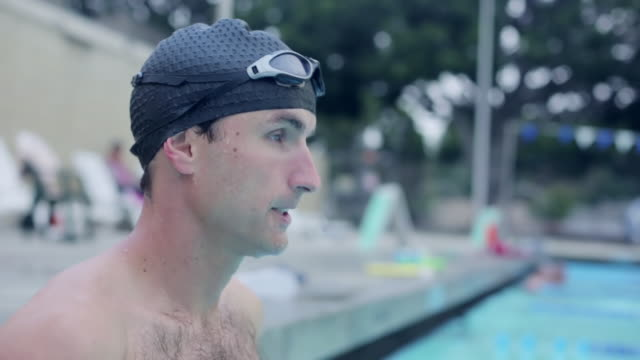 cu shot of swimmer putting on goggles and drops in pool / los angeles, california, united states  - swimming cap stock videos & royalty-free footage