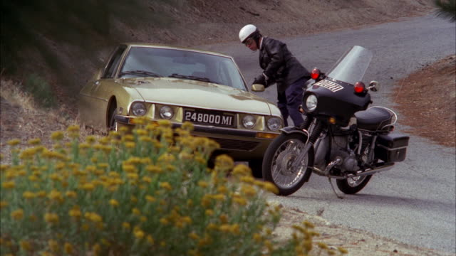 ms shot of switzerland motorcycle policeman stopping gold citroen sedan on a mountain highway - control stock videos & royalty-free footage